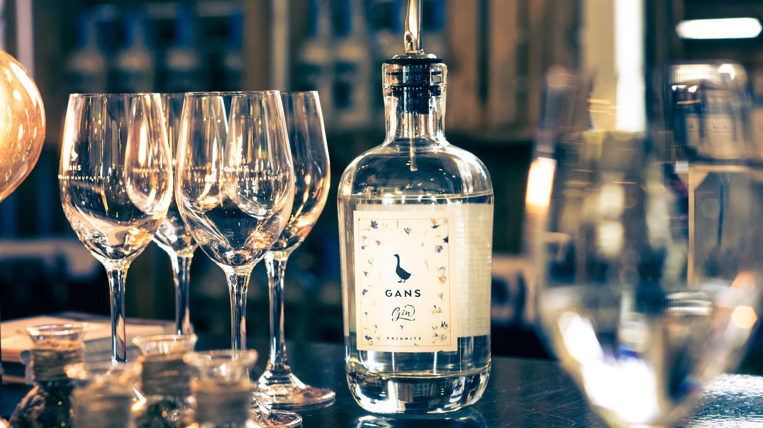Eine Flasche Gin der Marke GANS Feinbrand Manufakturmit Gläsern
